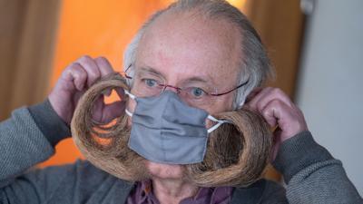 Jürgen Burkhardt, Bartträger und mehrfacher Bartweltmeister, demonstriert das Anlegen seines für ihn von einer Schneiderin angefertigten Mundschutzes.