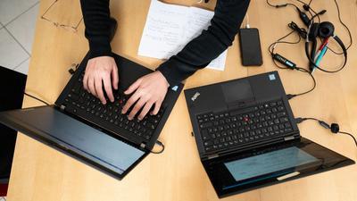 Eine Frau arbeitet am Küchentisch an ihren Laptops.