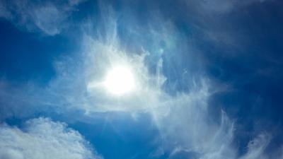 Die Sonne scheint am blauen Himmel durch Wolken hindurch.