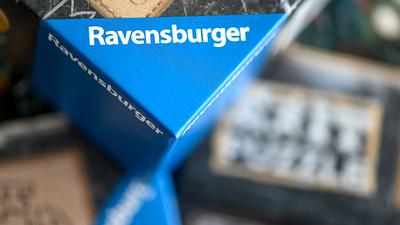 Spiele der Marke Ravensburger liegen übereinander auf einem Tisch.