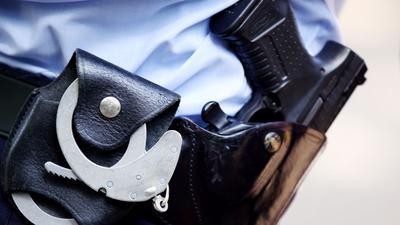 Ein Polizist mit Handschellen und Pistole am Gürtel.