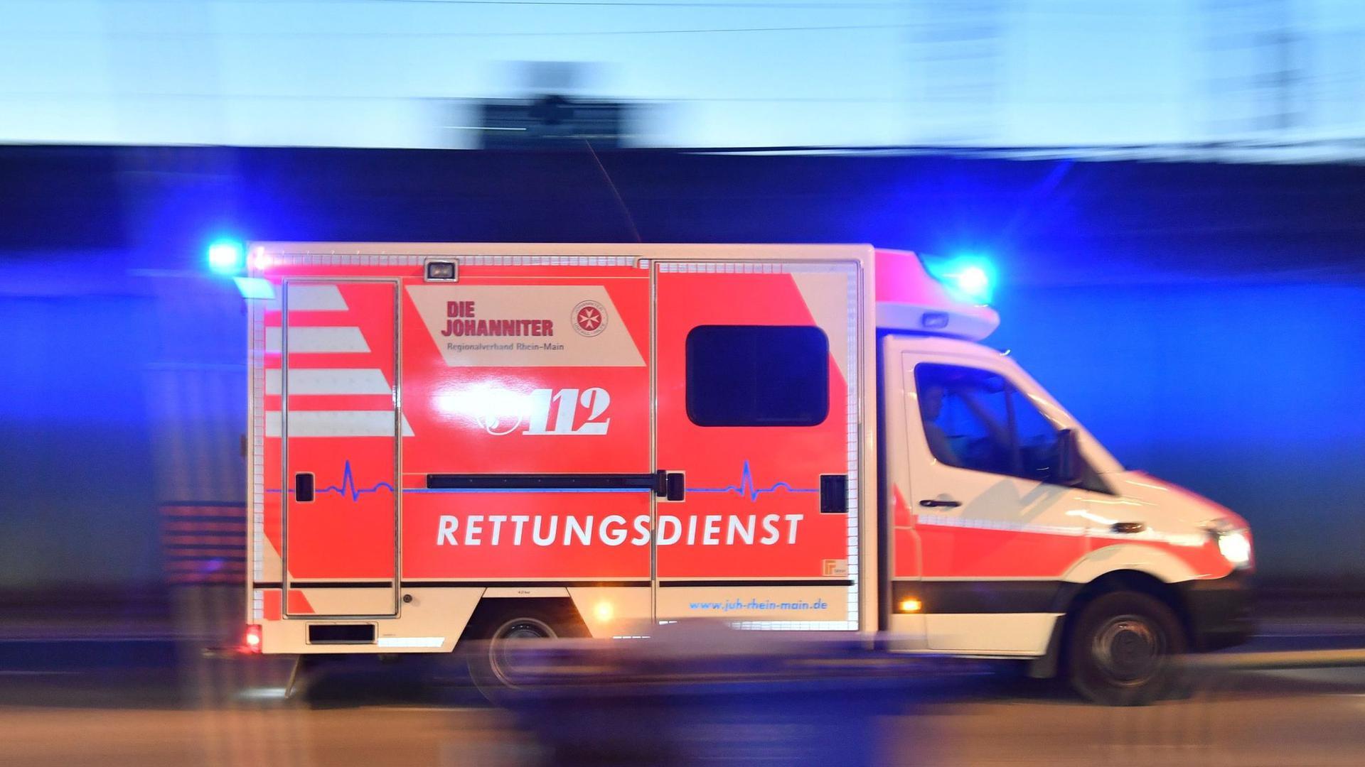 Ein Rettungswagen ist mit eingeschaltetem Blaulicht im Einsatz.