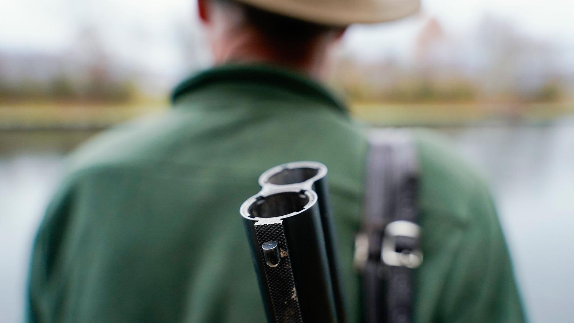 Ein Jäger steht mit seinem Gewehr in seinem Jagdrevier.