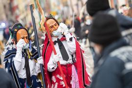 Narren mit OP-Masken über ihren Gesichtsmasken gestikulieren am Fastnachtsmontag vor Polizisten.