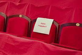 """Ein Zettel mit der Aufschrift """"Sitzplatz Freigegeben!!!"""" hängt an einem Sitzplatz im leeren Zuschauerraum eines Theaters."""