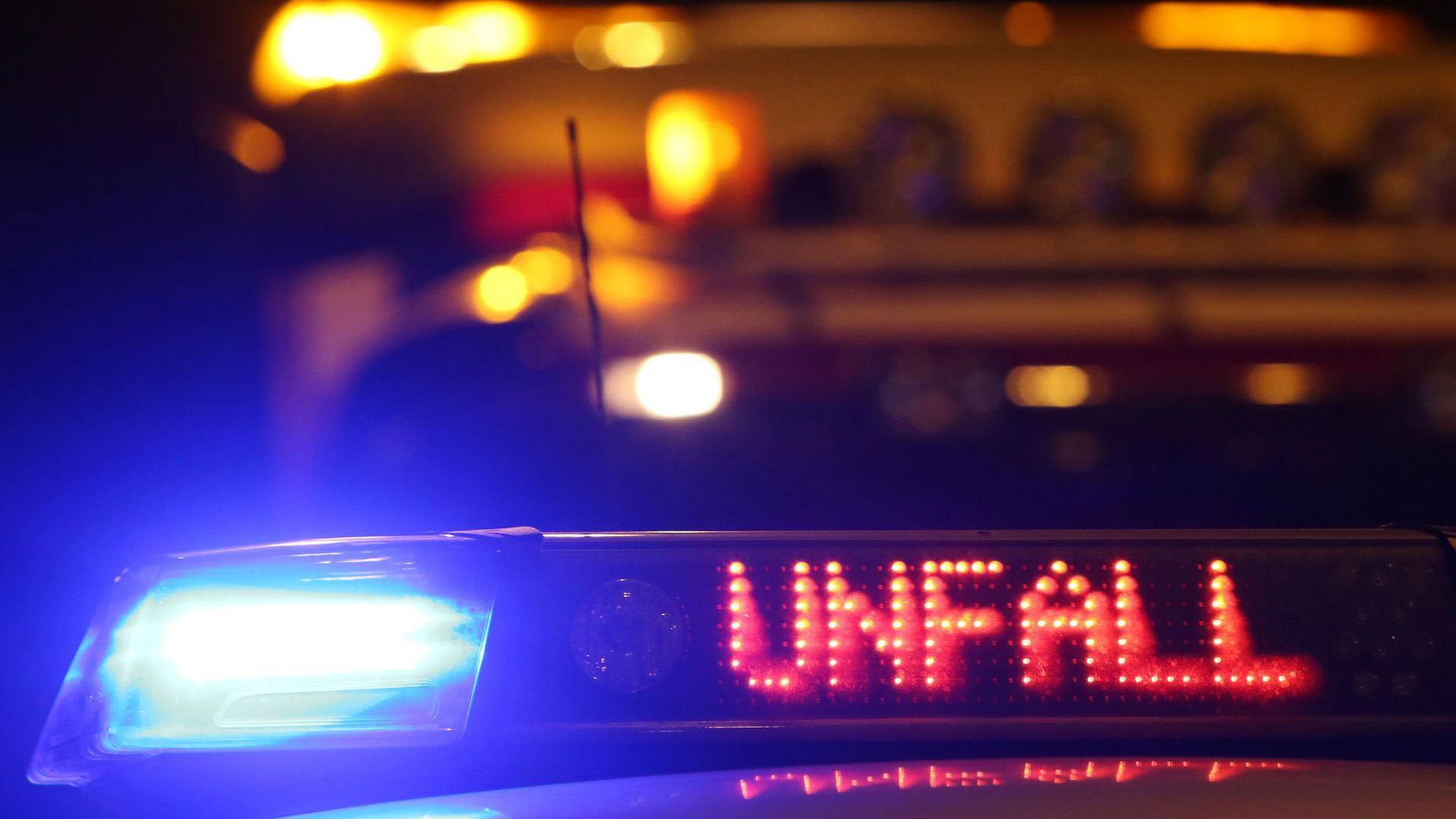 Ein Polizeiwagen steht mit eingeschaltetem Blaulicht an einer Unfallstelle.