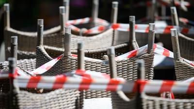 Gestapelte Stühle eines Restaurants sind mit Absperrband umgeben.