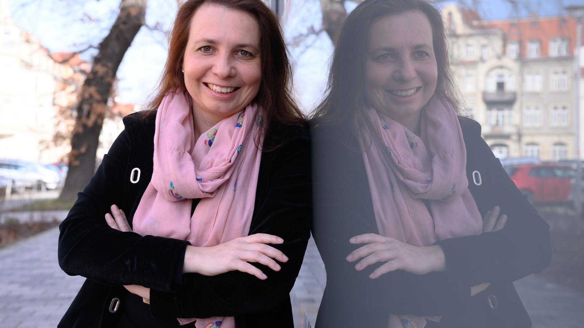 Angela Francke, Verkehrswissenschaftlerin, lehnt an einer Fensterscheibe.