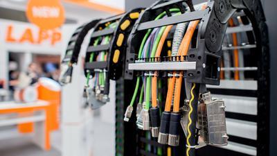 Mehrere Kabel hängen am Stand des Unternehmens Lapp bei einer Messe.