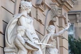 Vor einem Gerichtsgebäude steht u.a. eine Statue der Justitia.