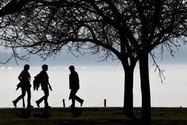 Spaziergänger gehen auf einem Wanderweg am Bodensee.