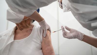 Eine Krankenpflegerin impft im Impfzentrum in der Paul-Horn-Arena in Tübingen eine Frau.
