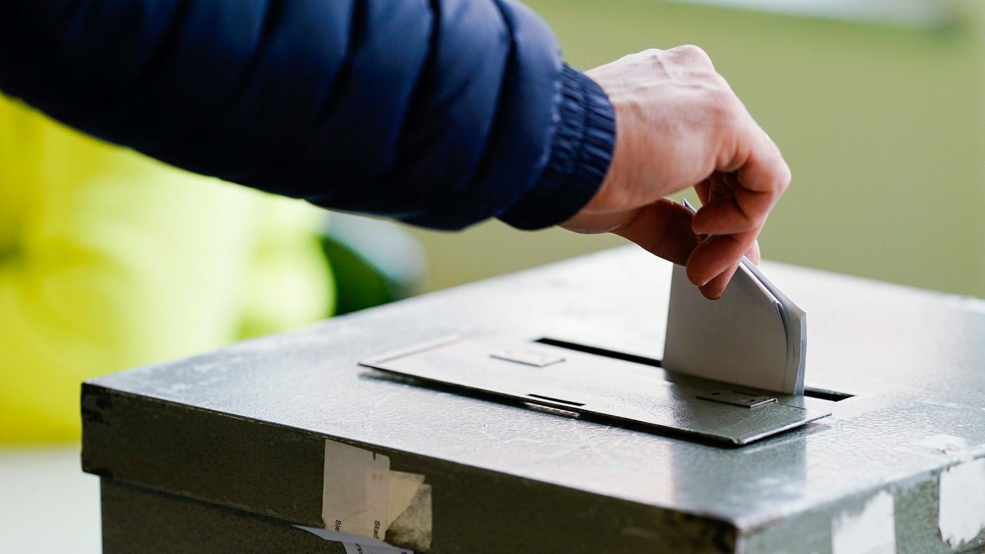 Ein Wählerin wirft in einem Wahllokal ihren Stimmzettel in die Wahlurne.