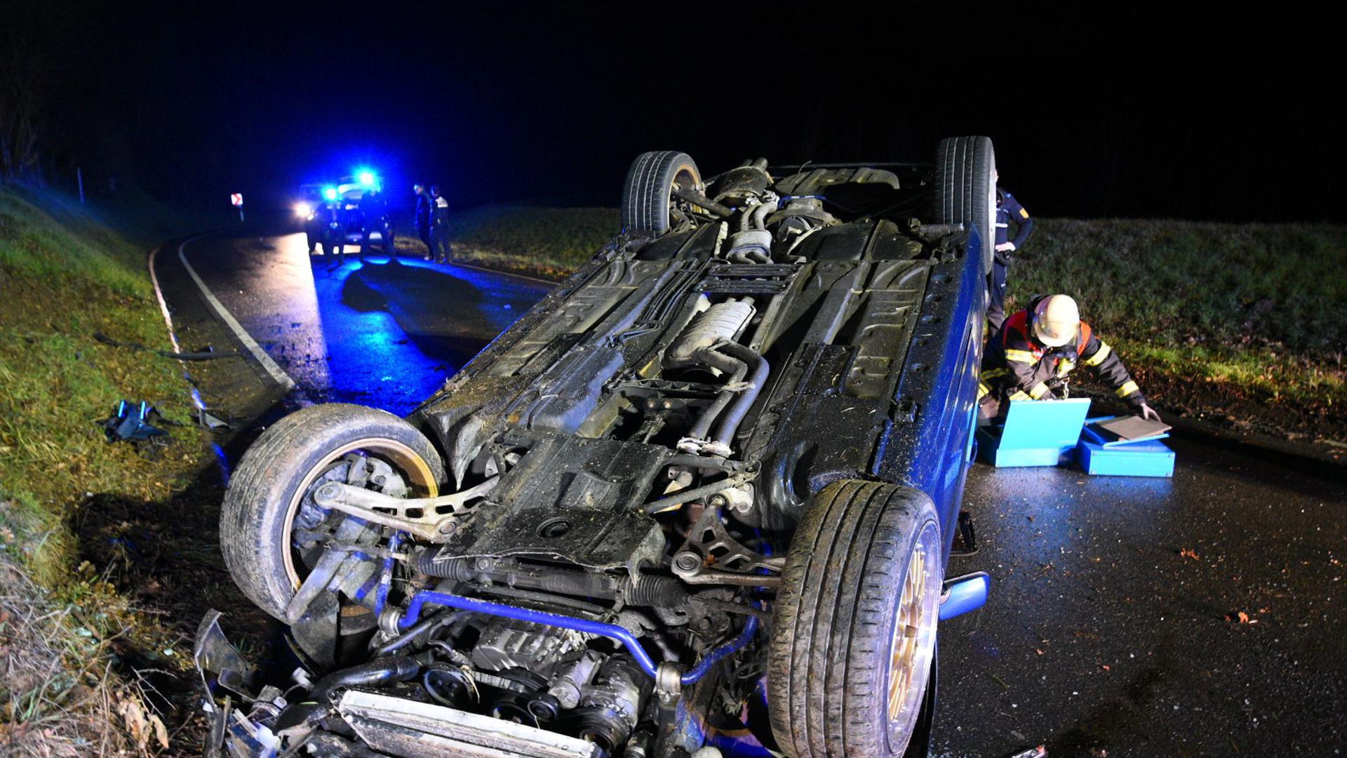 Nach einem Verkehrsunfall liegt ein Fahrzeug auf dem Dach auf der Straße.