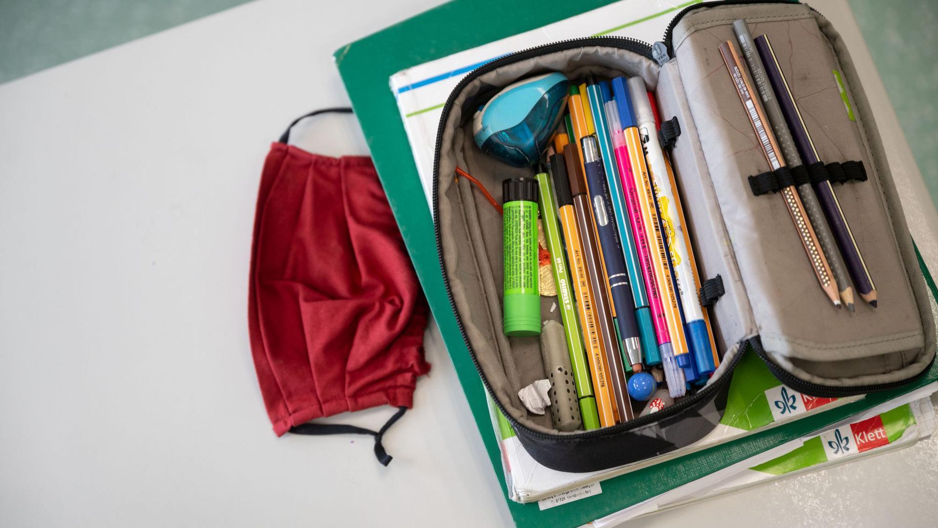 Eine Mund-Nasen-Bedeckung liegt neben einem Mäppchen und Schulbüchern auf einem Schultisch.