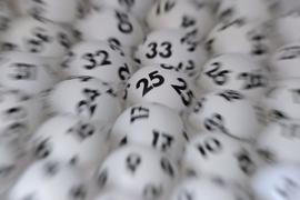 Lottokugeln liegen in einem Ziehungsgerät.