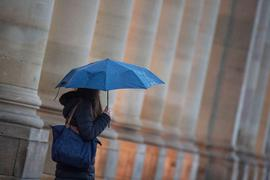 Eine Passantin geht bei Regen durch die Stadt.