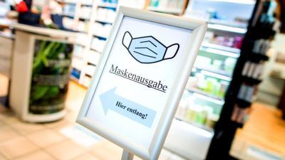 """Ein Schild mit der Aufschrift """"Maskenausgabe"""" steht im Eingang einer Apotheke."""