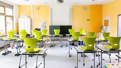 Stühle stehen auf Tischen in einem leeren Klassenzimmer einer Realschule.