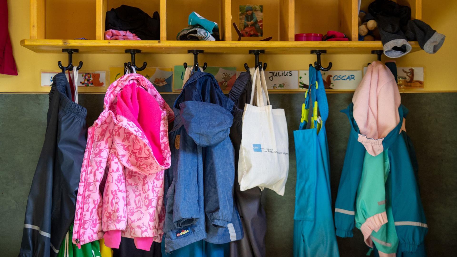 Jacken und Taschen hängen im Eingangsbereich in einem Kindergarten.