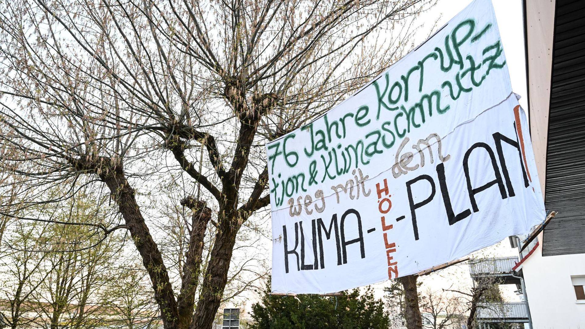 """Ein Plakat mit der Aufschrift """"76 Jahre Korruption und Klimaschmutz! Weg mit dem Klima-Höllen-Plan!"""" hängt am Bürogebäude des CDU-Kreisverbands Ravensburg."""