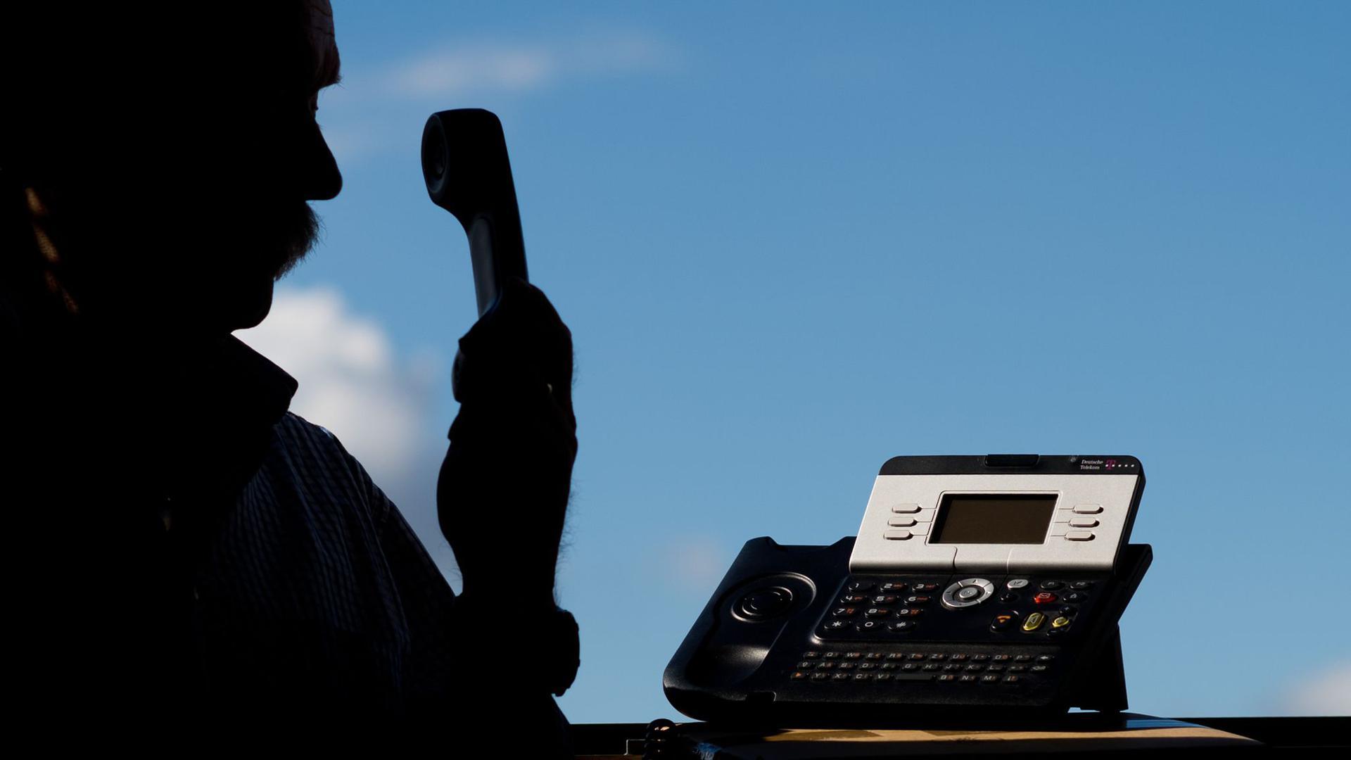 Ein Mann hält einen Telefonhörer in der Hand.