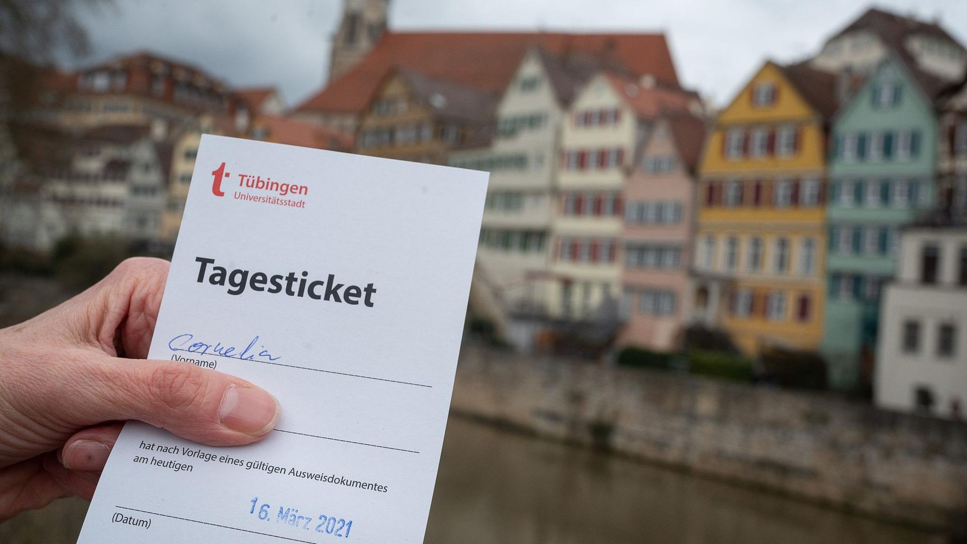 """Eine Frau zeigt am Neckar ihr """"Tagesticket"""", das aufgrund eines negativen Testergebnis bei einem Corona-Schnelltest ausgestellt wurde."""