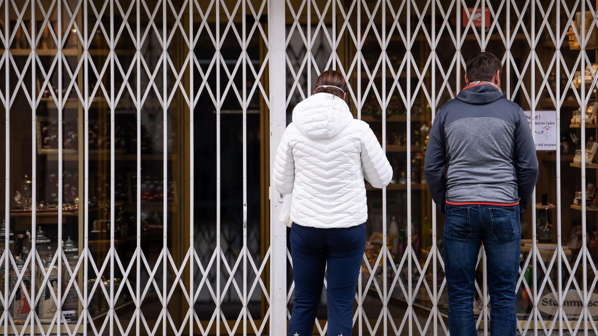Zwei Passanten stehen in einer Fußgängerzone vor einem geschlossenen Geschäft.