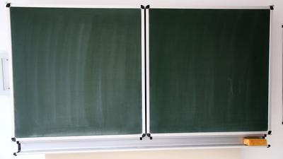 Eine Schultafel steht in einem Klassenzimmer in einer Schule.