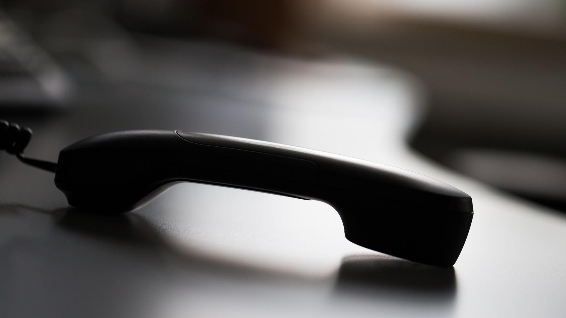 Ein Telefonhörer liegt auf einem Tisch.