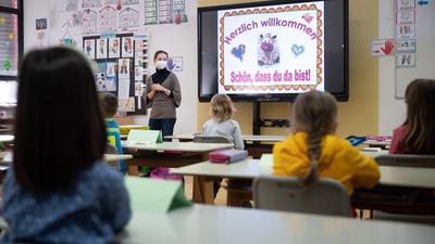 Eine Lehrerin mit FFP2-Maske unterrichtet in einer ersten Klasse.