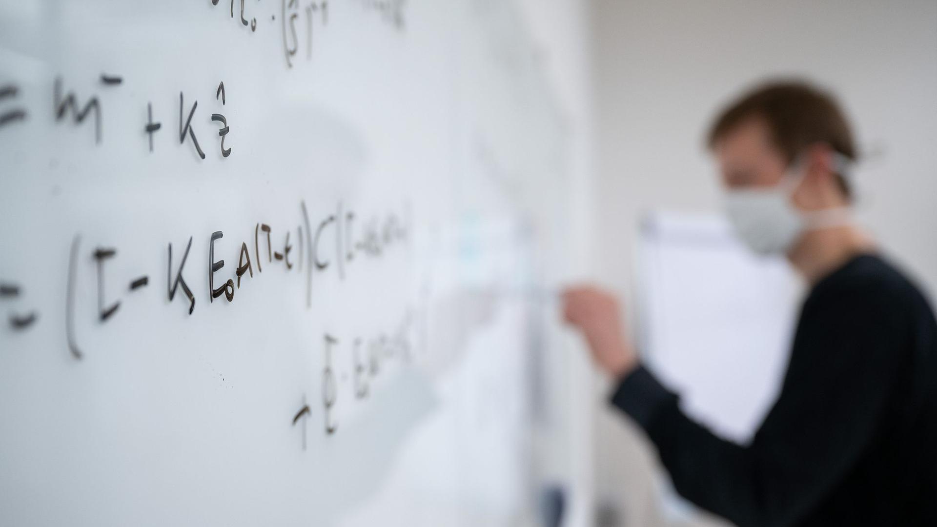 Mathematische Formeln werden in der Universität Tübingen an ein Whiteboard geschrieben.