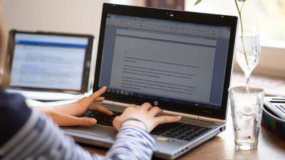 Eine Schülerin sitzt in einem Arbeitszimmer und arbeitet für die Schule.