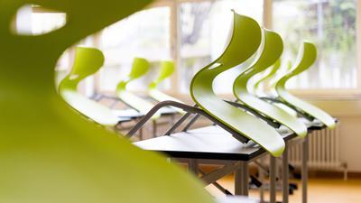 Stühle stehen auf Tischen in einem leeren Klassenzimmer.