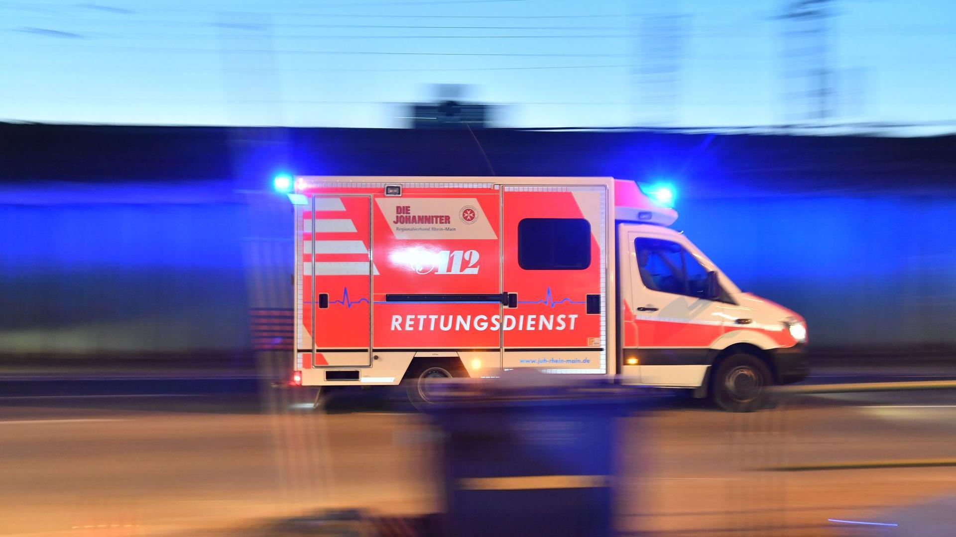 Ein Rettungswagen mit eingeschaltetem Blaulicht fährt auf einer Straße.