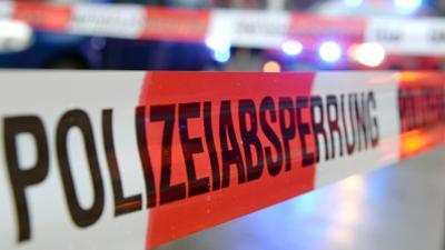"""Ein Flatterband mit der Aufschrift """"Polizeiabsperrung""""."""