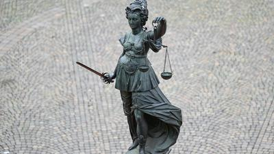 Die Statue der Justitia steht mit einer Waage und einem Schwert auf einem Platz.