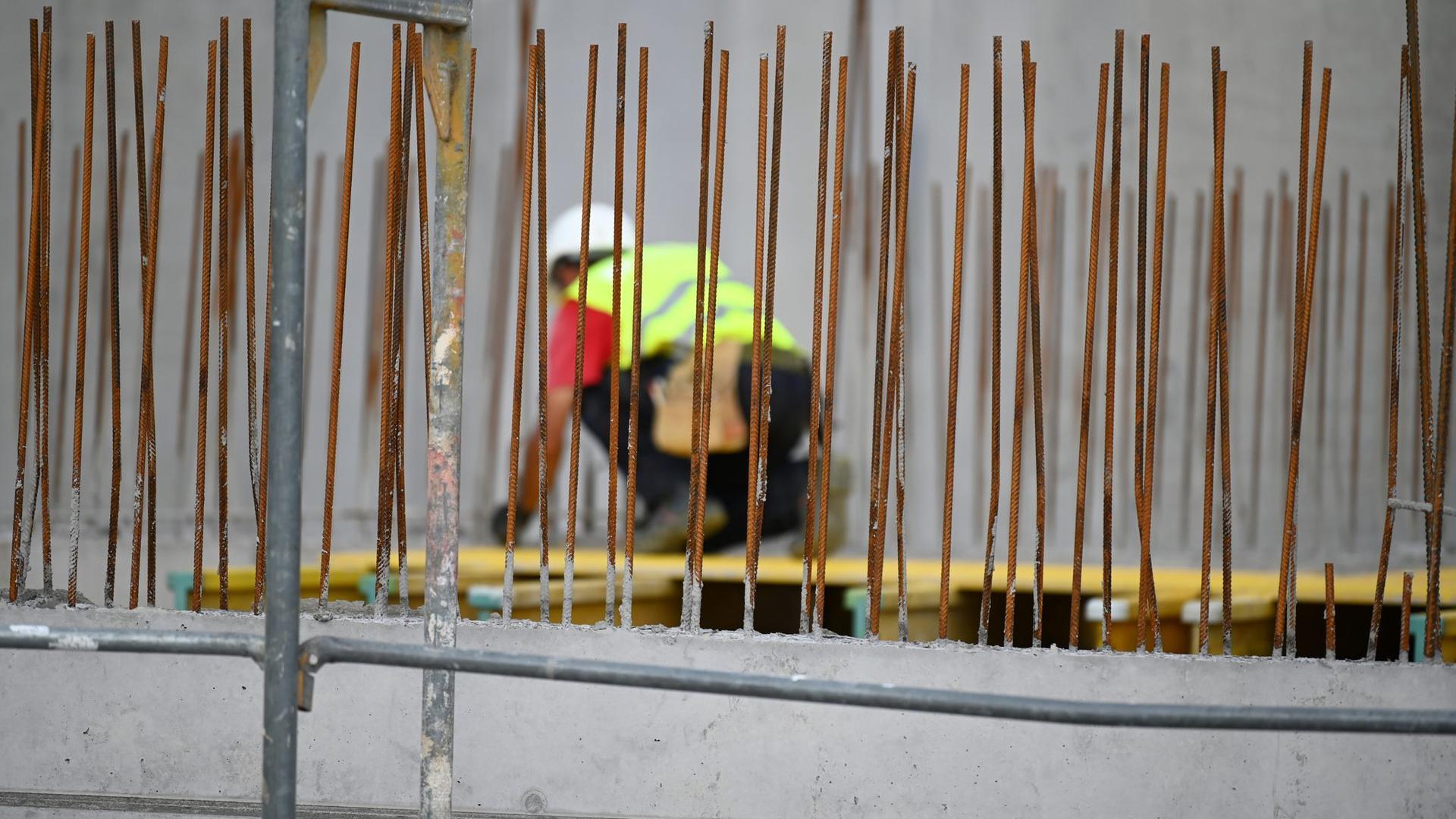 Ein Handwerker arbeitet auf einer Baustelle an Betonstahlträgern.