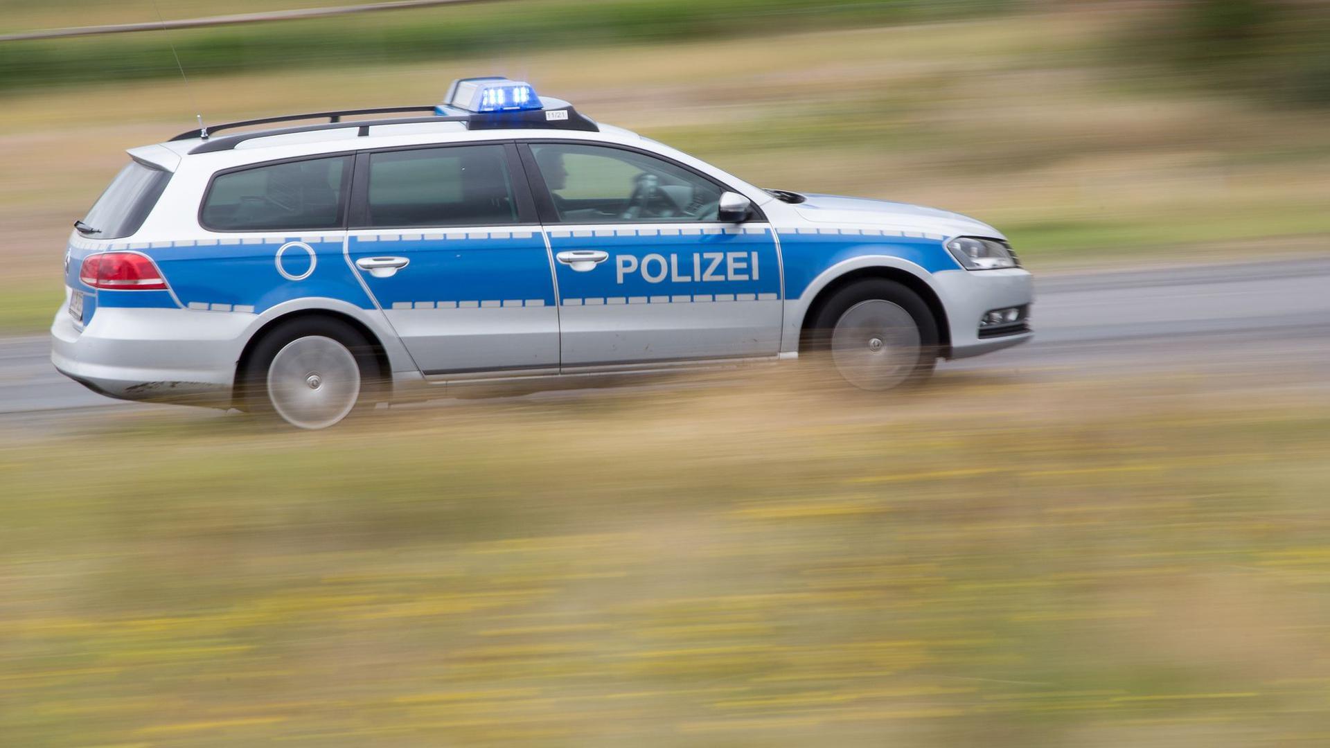 Ein Streifenwagen fährt mit Blaulicht über eine Straße.