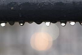 Regentropfen hängen an einem Geländer.