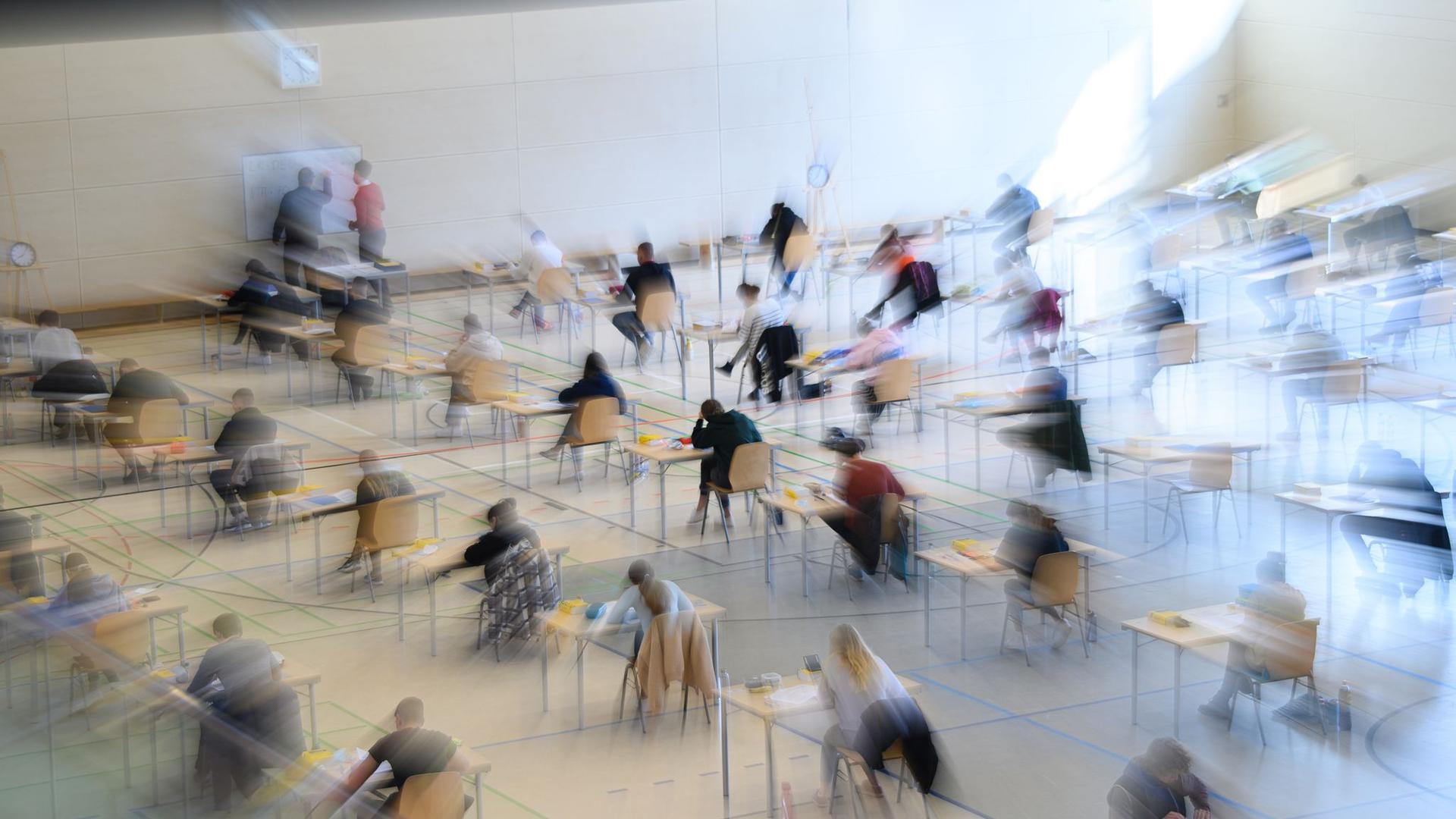 Mit weitem Abstand sitzen Schüler zur Abiturprüfung an ihren Tischen.