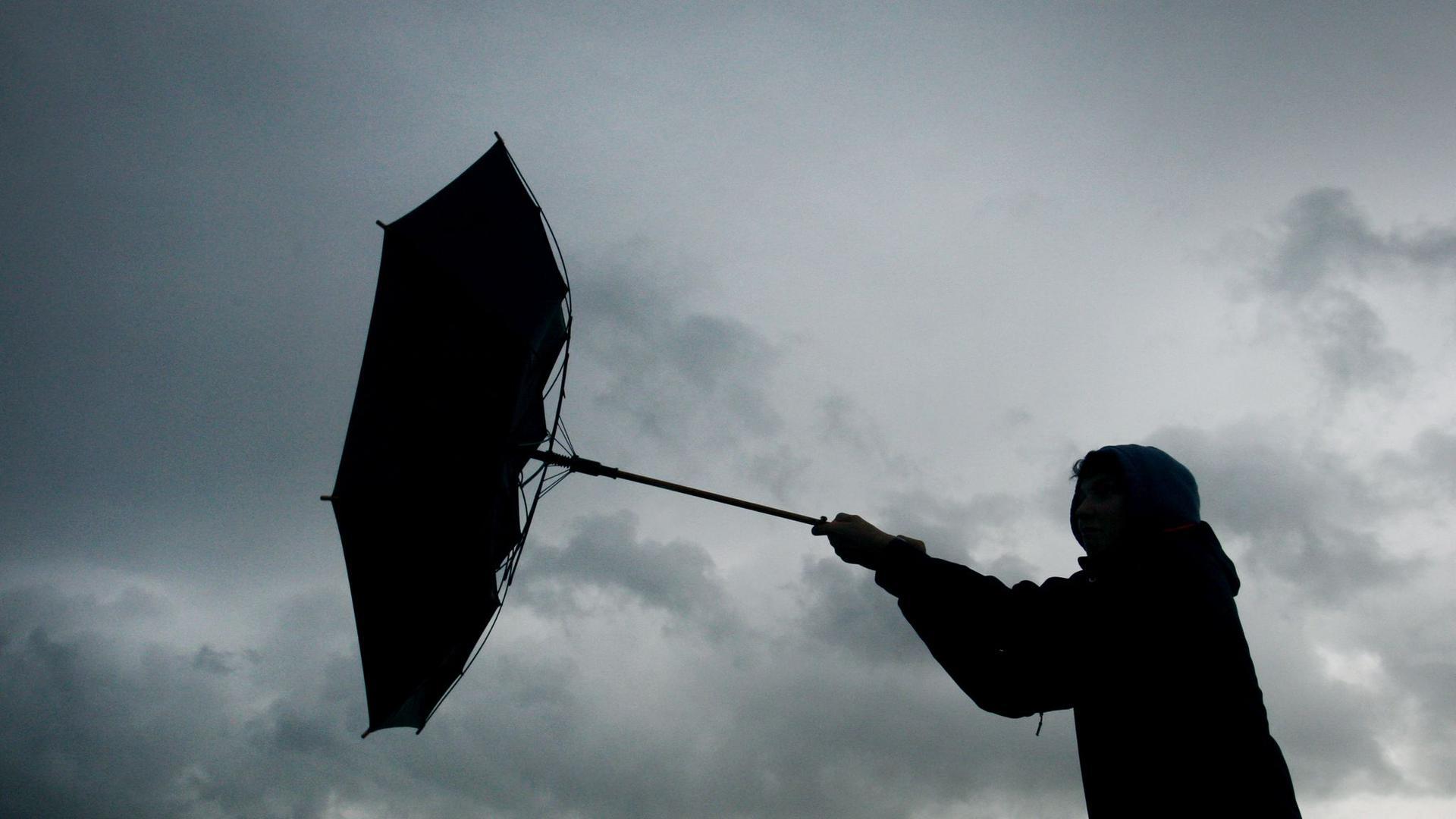Der Regenschirm eines Spaziergängers wird von einer Windböe erfasst.