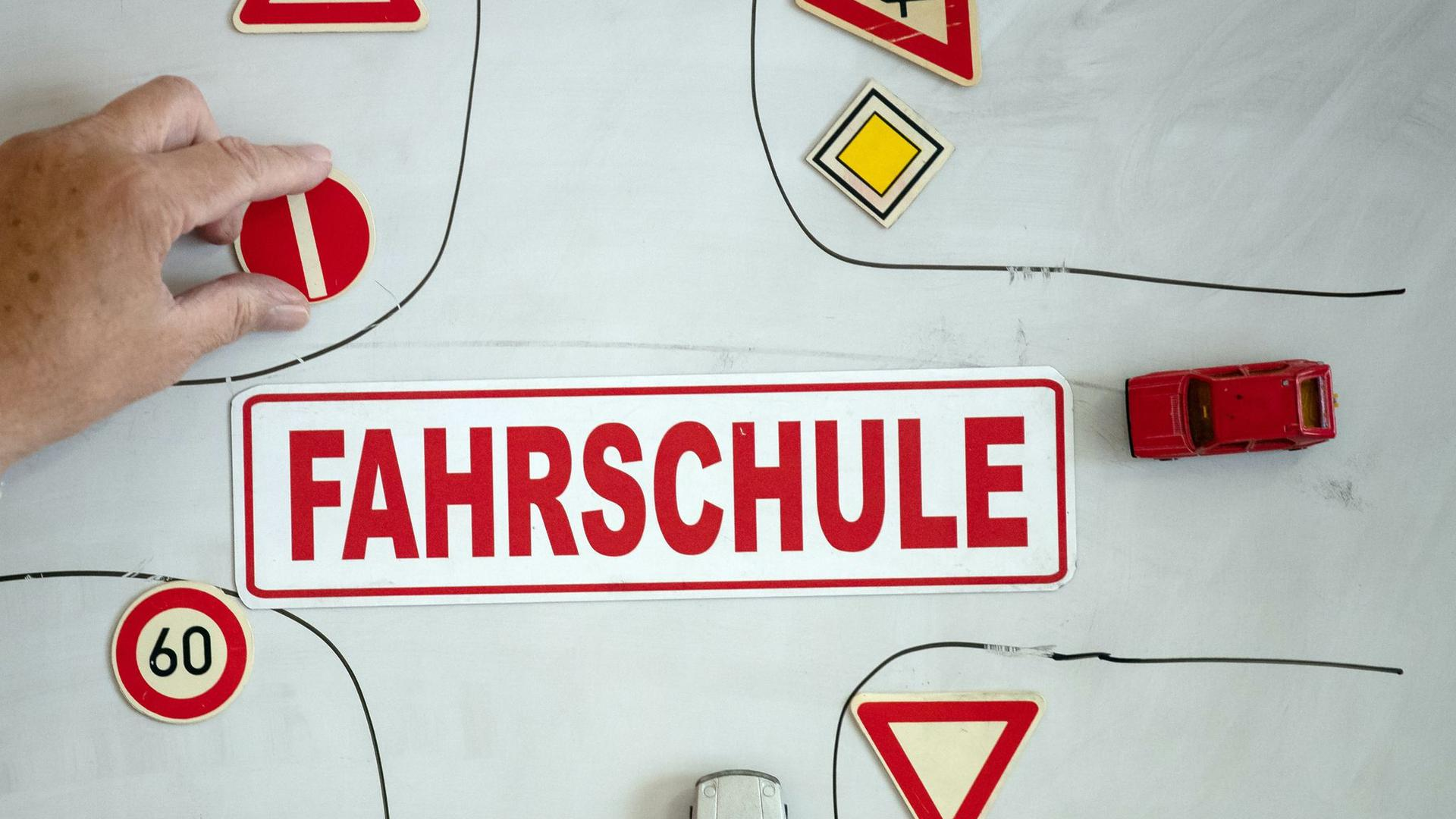 """Ein Magnet mit der Aufschrift """"Fahrschule"""" an einer Wandtafel mit verschiedenen Verkehrsymbolen."""
