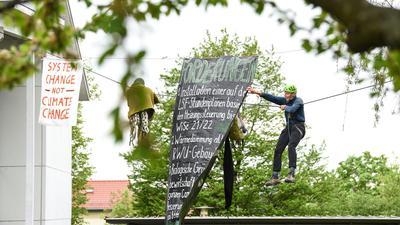 Professor Wolfgang Ertel (r) hängt an einem Seil neben einem Transparent mit Forderungen.