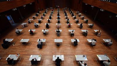 Studierende sitzen während einer Prüfung in einer Halle.