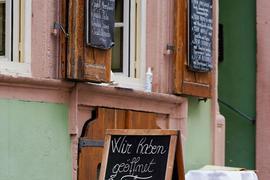 """Ein Schild mit der Aufschrift """"Wir haben geöffnet"""" steht vor einem Restaurant in der Innenstadt."""