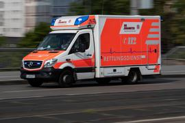 Mit eingeschaltetem Blaulicht ist ein Rettungswagen im Einsatz.
