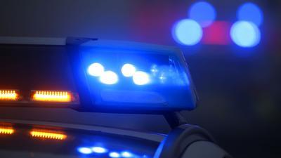 Auf einem Polizeifahrzeug leuchtet das Blaulicht.