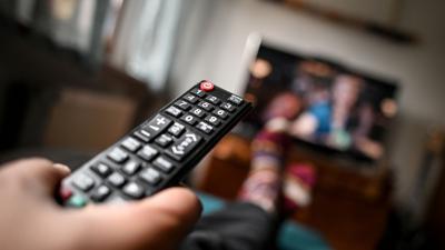 Ein junger Mann sitzt mit einer Fernbedienung vor dem Fernseher.