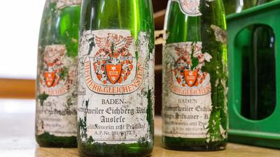 Alte Weinflaschen mit verwitterten Etiketten stehen im Weingut Freiherr von Gleichenstein auf einem Tisch.